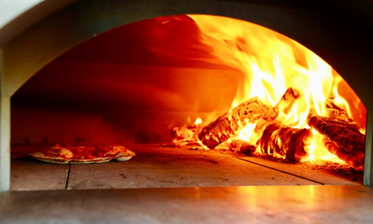 wood fired pizza cooking in pizza oven