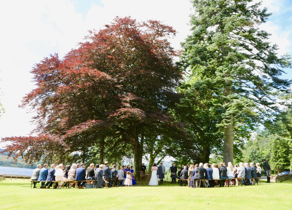 An outdoor wedding ceremony taking place at Altskeith Country House under the beech tree.