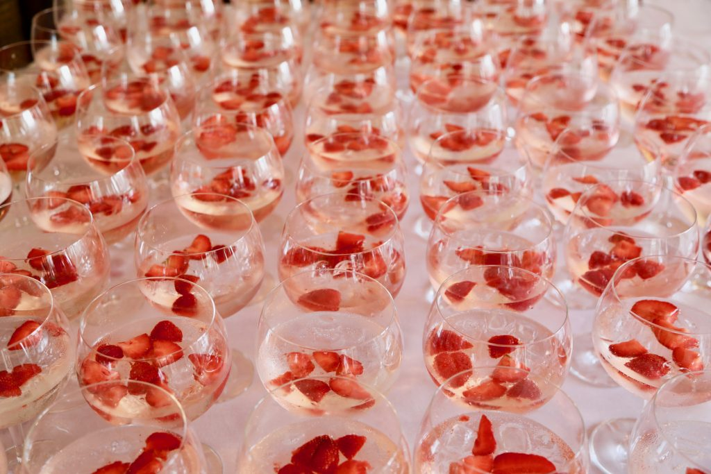 Gin and tonic with a strawberry garnish lined up for guests during a drinks reception