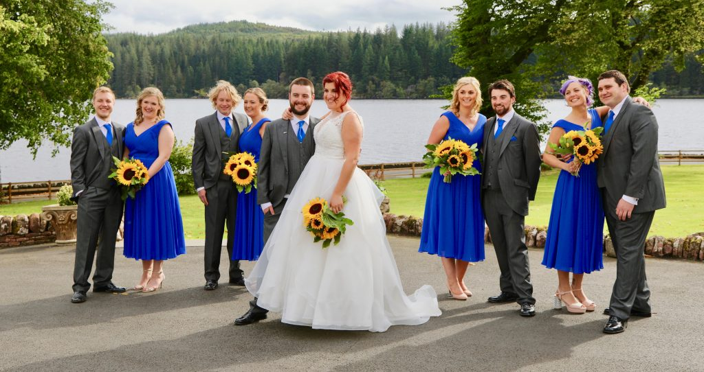The bride and groom with their wedding party having photographs taken in the gardens at Altskeith Country House